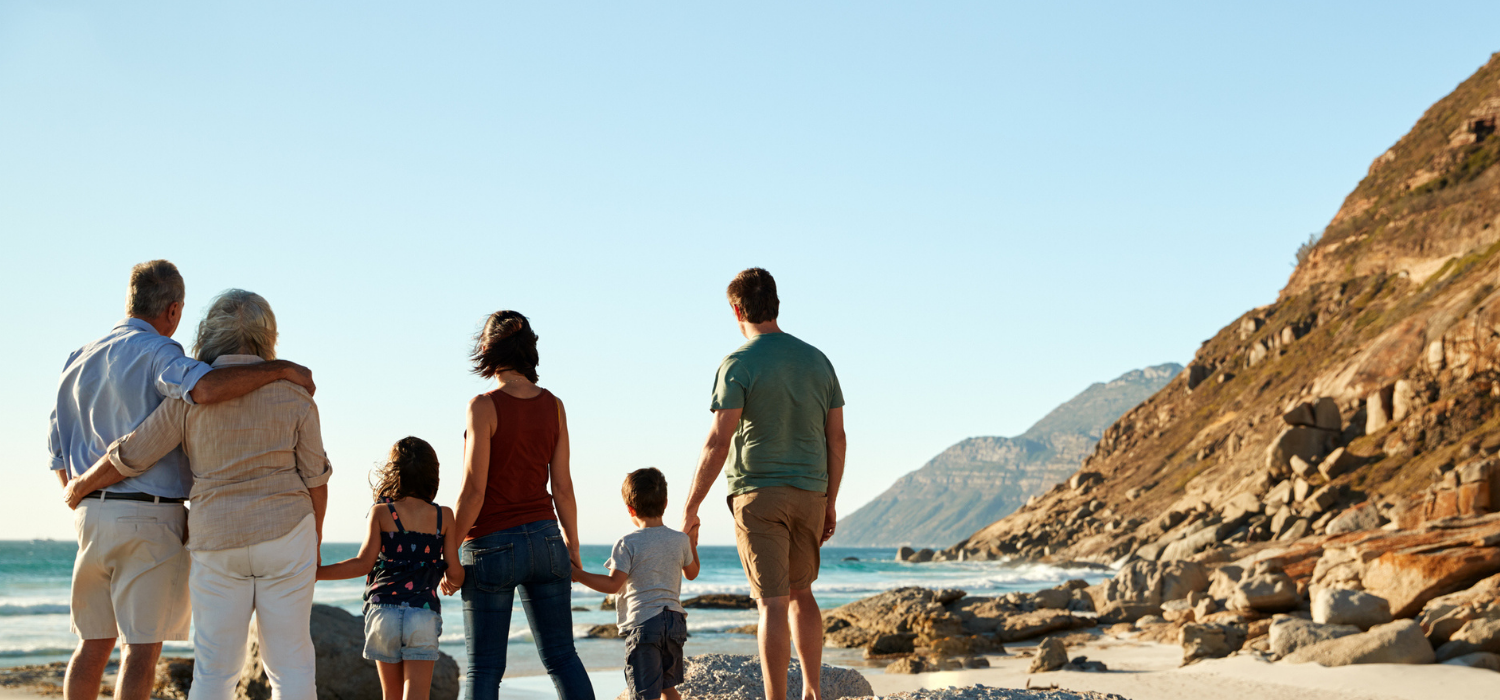 A family of six, standing on a pristine beach, looking out into the sea in a sunny climate